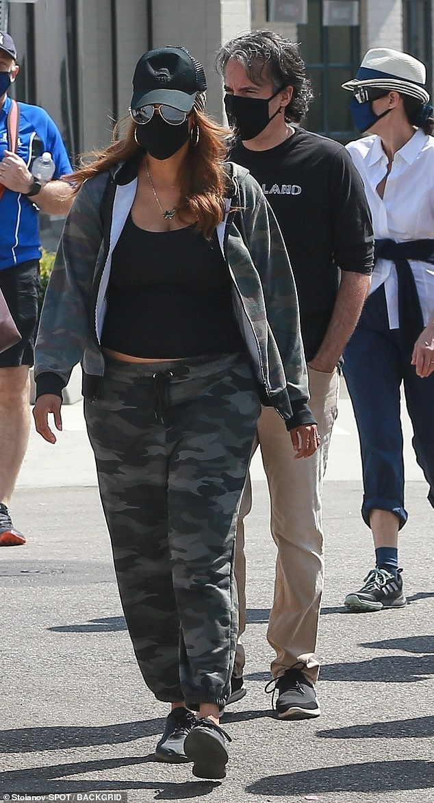 Covered up: The model, 46, wore a black tank with camo pants and jacket. She had a baseball cap pulled down over her hair and wore a pair of large sunglasses and a cloth face mask