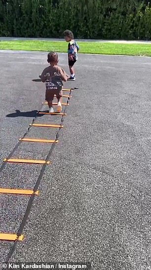 Your turn: Kim then encouraged her youngest son Psalm to attempt the agility ladder for himself, instead of watching his siblings and cousin from the sidelines