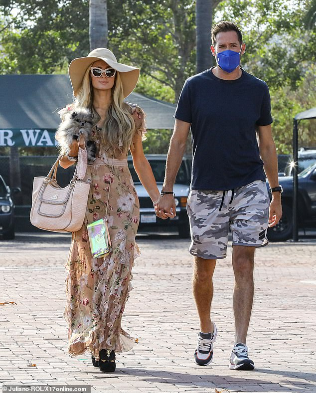 Couple: Paris, 39, was dressed in a sleeveless floral-themed frock with thigh-high split and platform shoes. She wore a large floppy sun hat and cat's eye sunglasses
