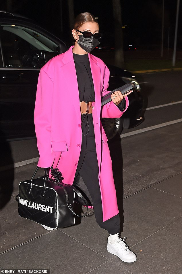 Jet set: The duo were seen strutting into Milan airport looking typically glamorous as they prepared to fly home to Los Angeles after Fashion Week. Hailey wore a matching black crop-top and sweatpants combo, flashing her taut waist. She covered up with a neon pink trench