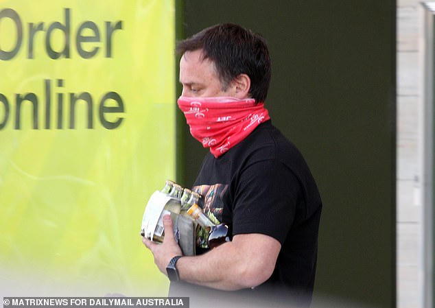 Bandannas such as this one worn by a man at Edithvale Woolworths, Melbourne, in August, are now banned unless you are also wearing a face mask underneath