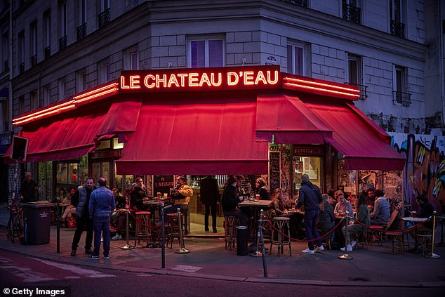 Paris is set to enter a strict second lockdown in attempt to slow the spike in coronavirus cases. Pictured: Parisians drink outside at a bar last night before the restrictions bare introduced