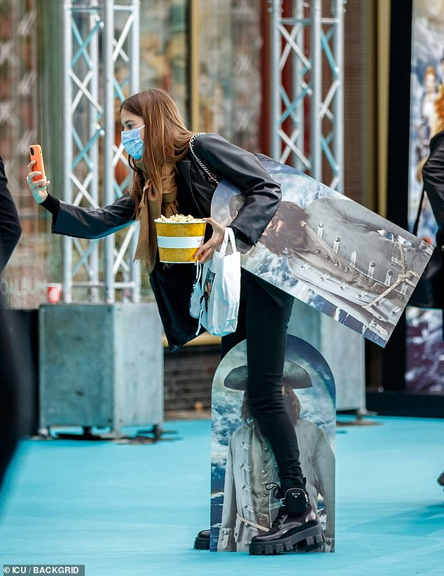 Treats Galore: The German model opted for a comfy leather jacket and skinny black jeans as she snapped a photo with her bag of goodies and popcorn from the premiere