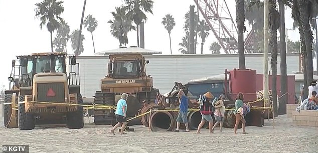 The tractor driver felt a bump and at first thought he had hit a dip but then turned around and saw the woman in the sand. Beachgoers walk past roped off tractors at the beach