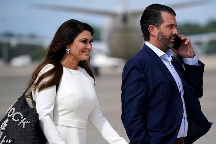 Donald Trump Jr. and Kimberly Guilfoyle walk across the tarmac to board Air Force One at Andrews Air Force Base before flying to Cleveland