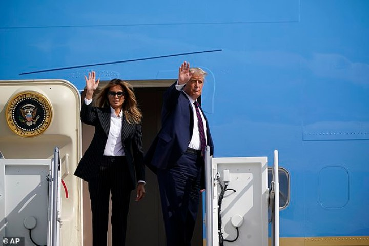 President Donald Trump and first lady Melania Trump wave before boarding Air Force One to travel to Cleveland