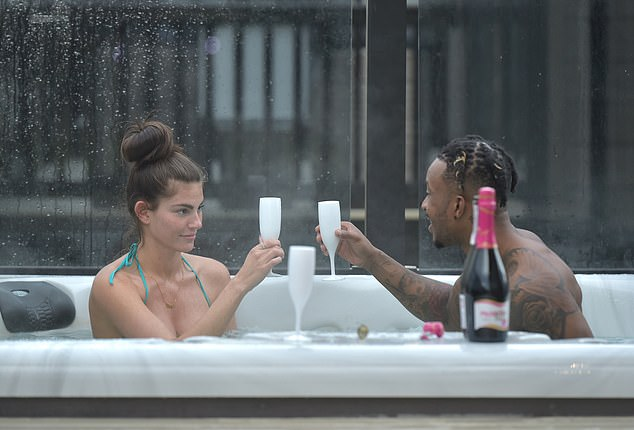 Cheers! The couple clinked glasses while relaxing in the hot tub