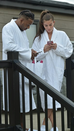 Cosy: The couple wrapped up in white towels as they received their alcohol delivery