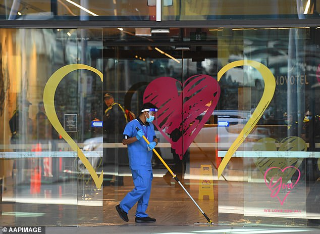 Private security guards have been pulled from a Melbourne quarantine hotel and replaced by police. Pictured: Cleaning staff at the hotel on Thursday