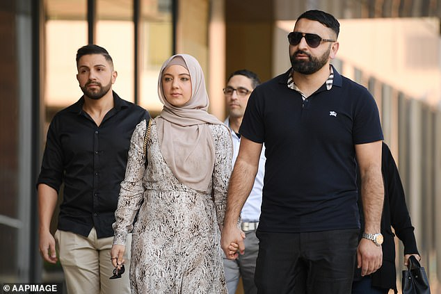 Victim Rana Elasmar holding hands with her husband Azzam as they arrive with supporters at Parramatta District Court on Thursday. Lozina had shouted 'Muslims raped my mum' at the pregnant hijab-wearing woman and repeated the same phrase in court