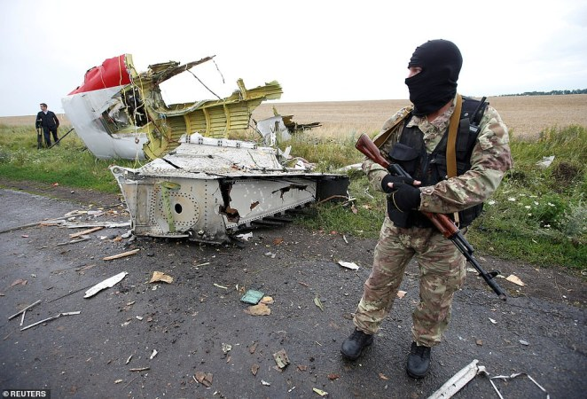 A pro-Russian separatist stands at the crash site of MH17 in Ukraine, a disaster which investigators blamed on a missile transported from a Russian military base
