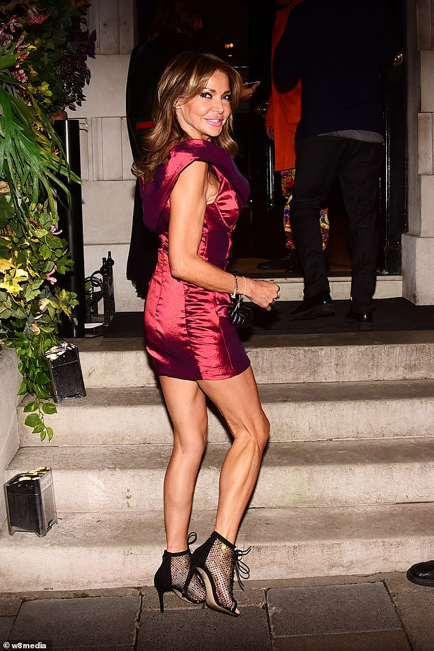 In she goes: Dressed to the nines, the glam media personality slipped into a dark pink cocktail dress for her night out
