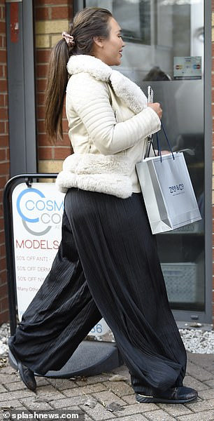 Living her best life: The 34-year-old appeared in a good mood when she walked inside dressed in a fur coat, black baggy pants and sneakers
