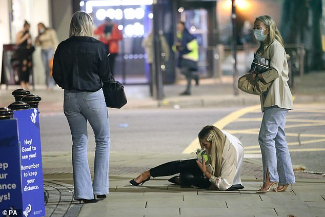 Three women out for the evening in Manchester. One woman is seen sitting on the floor enjoying a sandwich