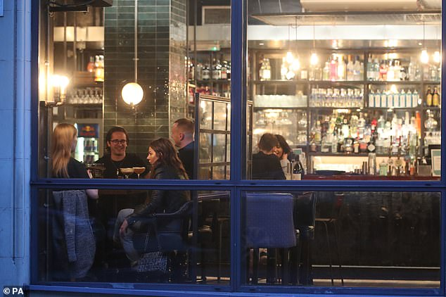 People enjoy drinks at a bar in Manchester. From Monday, bars and restaurants could be told to close