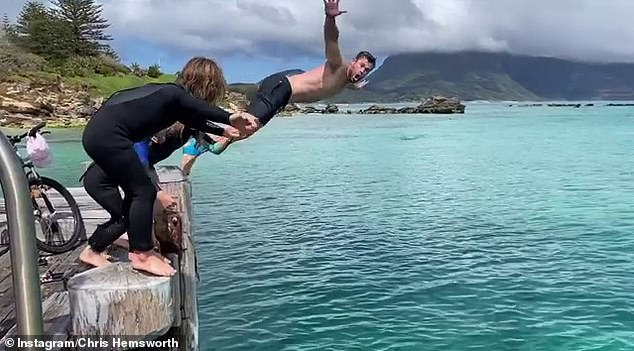 Jump: Chris shared a picture and video of himself jumping off a jetty and diving into the water with his kids and friends