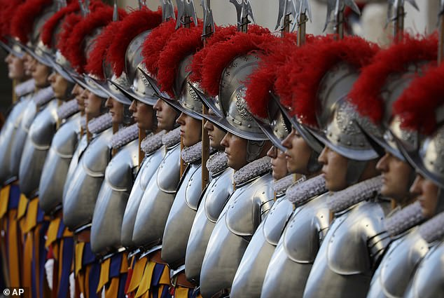 The guards, pictured here at attention on October 4, are instantly recognizable by their striped suits, ruffles, and feathered helmets and are a favorite sight for tourists visiting the Vatican.