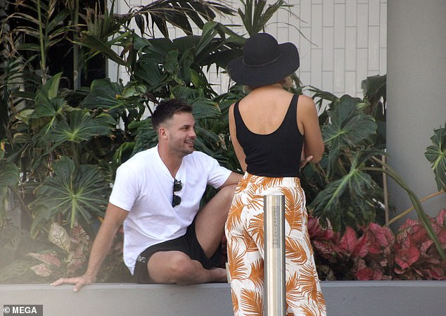 Relaxing: The 35-year-old wore a white T-shirt and black shorts as he sat on a wall outside a venue in Cairns