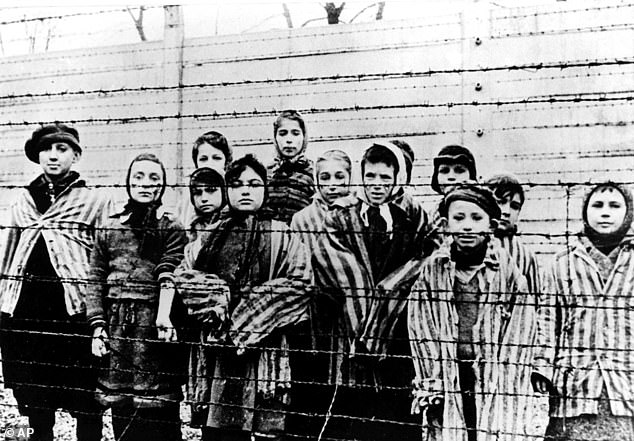 A picture taken just after the liberation of Auschwitz by the Soviet army in January, 1945, shows a group of children wearing concentration camp uniforms behind barbed wire fencing in the concentration camp