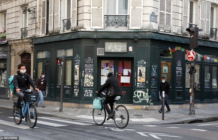 FRANCE:Cyclists ride past the Au Chat Noir bar in Paris which has been closed as part of stricter restrictions due to the coronavirus in Paris