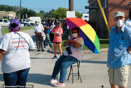 SAVANNAH, GEORGIA: Crystal Clark sits on a folding stool while holding an umbrella for shade as she waits in line to vote on Wednesday