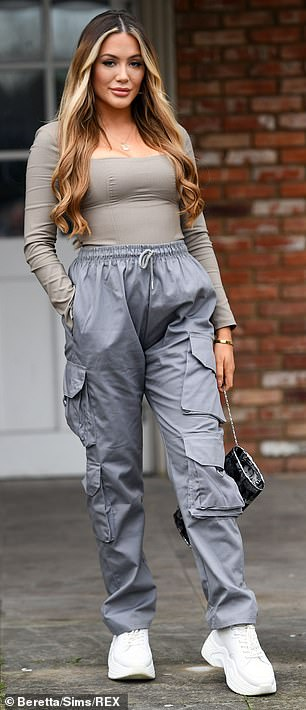 Neutral: Frankie woreslate grey waterproof trousers and a tight-fitting khaki top tucked in with white trainers