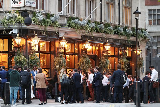 Drinkers outside a pub in Westminster last month. You will only be allowed to have a drink with friends from a different household at the pub outdoors from Saturday - and not indoors