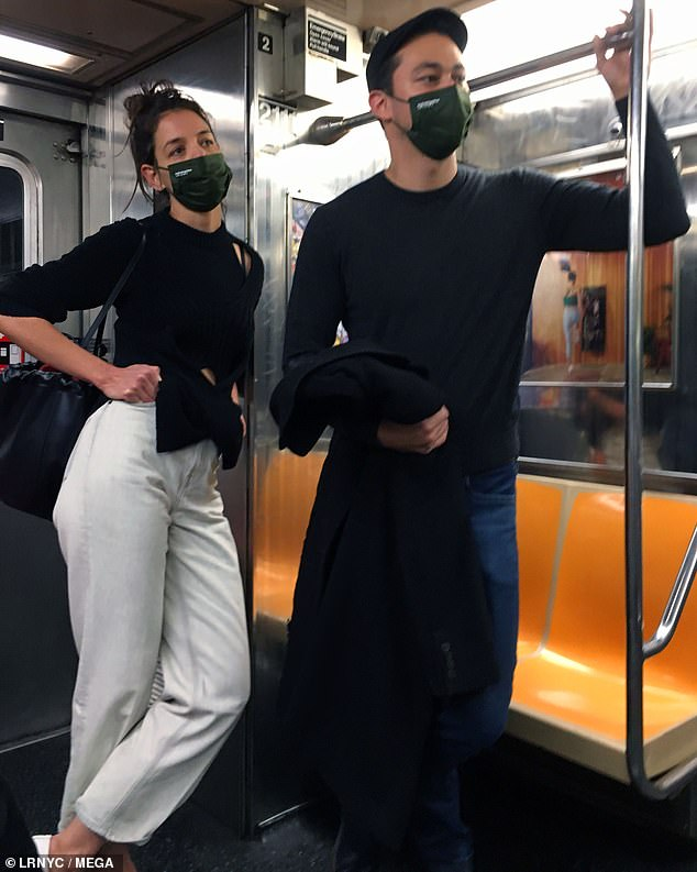 Wear a mask: She carried a black leather drawstring purse over her shoulder, as she took precautions against COVID-19 in a green face mask