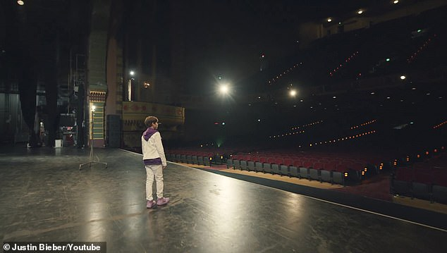 Stage: As the young Bieber walks out onto the stage in front of an empty arena, the adult Bieber sings, 'What if you'd had it all but nobody to call maybe then you'd know me'