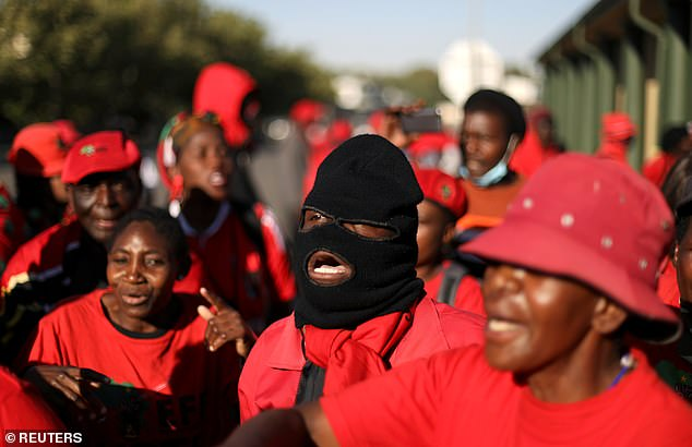 A protester wearing a balaclava mask joins supporters of the Economic Freedom Fighters in their signature red outfits as they march through Senekal today