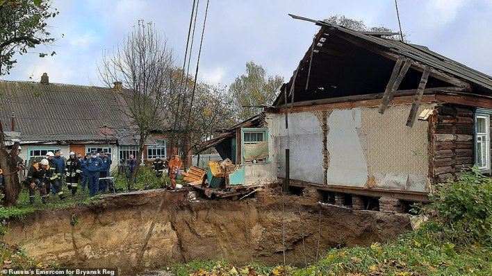 An entire house was swallowed up when an enormous sinkhole suddenly opened in a Russian village. The attached house (pictured above) escaped the fate of its neighbour