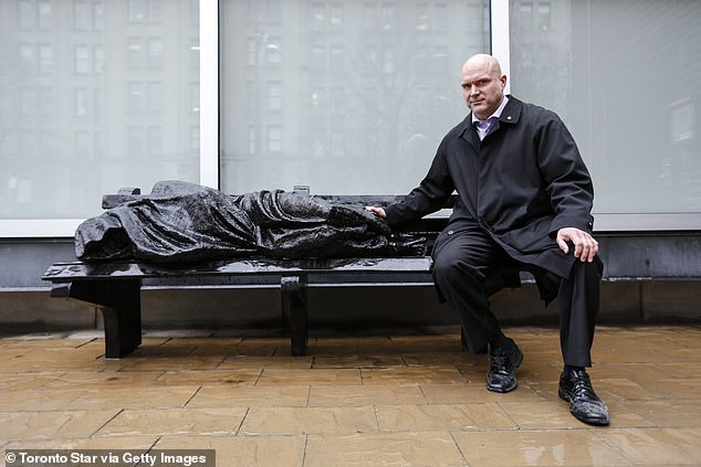 Canadian sculptor Timothy Schmalz is shown with his sculpture 'Jesus the Homeless' in front of the University of Toronto's Regis College. He's said the statue is 'meant to challenge people'
