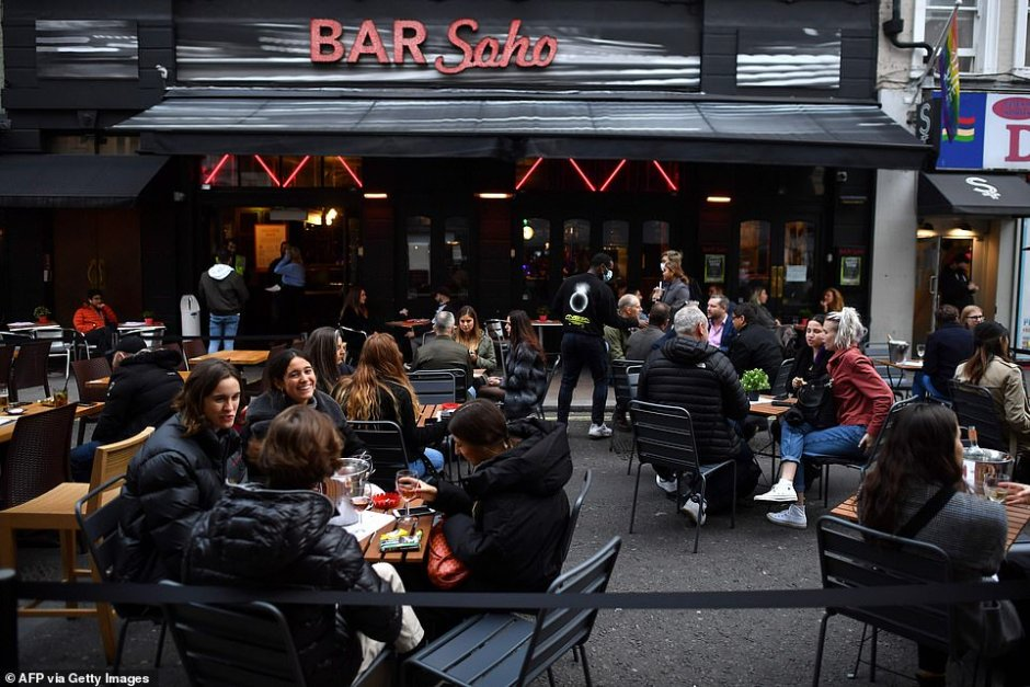 People enjoy their drinks outside at a bar in Soho, in the West End of London on October 16, 2020, as new restrictions on social gatherings and movement are set to come into force