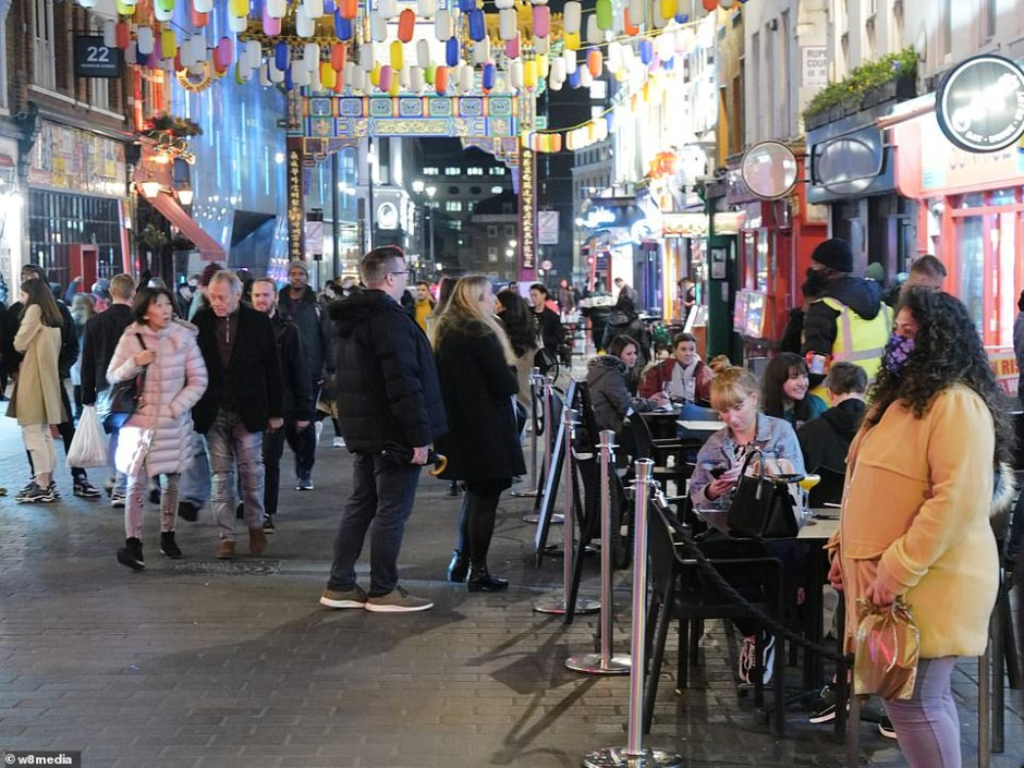 People queued for access to a bar in China Town this evening. Those seated outside were forced to wear coats in the harsh autumn weather