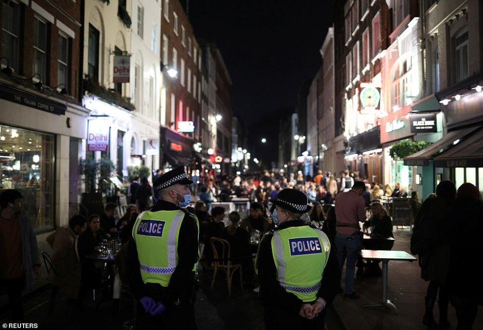 Police officers stood nearby venues as the time approached 10pm ready to enforce coronavirus restrictions after the curfew in Soho, London