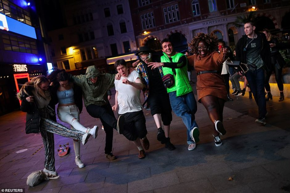 A group ignored social distancing and joined in on what looks like a can-can dance in the middle of Soho as pubs closed