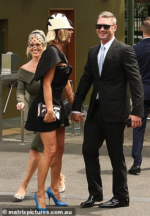 Smile: The couple also appeared to be laughing with a friend as they walked hand in hand through Randwick Racecourse