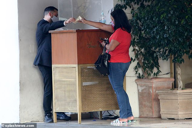 Heading out: Mindy was seen exiting the hotel and paying the valet to have her car brought up to the front