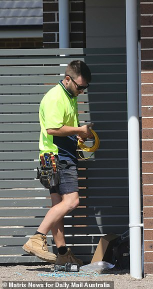 On another property a tradie works on a nearly completed building
