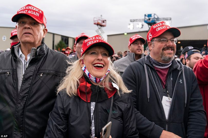 Supporters smile as they listen to the president speaking in Michigan. Many wore red MAGA hats but very few wore face masks