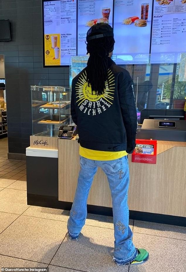 Casual cool: Quave stood in front of a McDonald's menu in blue jeans, Dickies jacket over mustard-yellow shirt and green sneakers