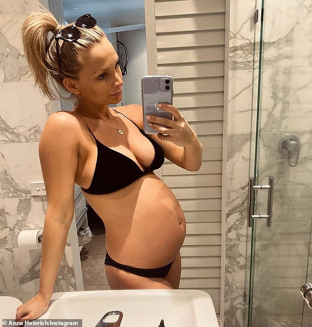 Almost there! Anna Heinrich (pictured) is set to welcome her first child, a girl, with husband Tim Robards.And on Sunday, the 33-year-old publicly reminisced about the size of her bump in September as she is no longer able to fit into her bathers - nor her wedding ring