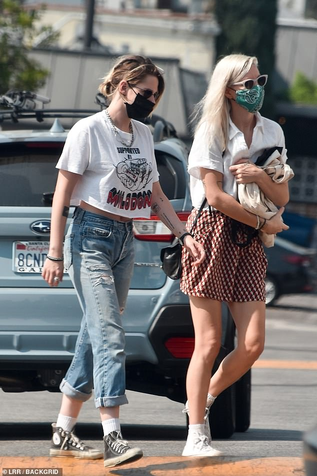 Masked up:The Twilight star wore a midriff-baring cropped white t-shirt for the outing, paired with distressed jeans rolled up at the calves