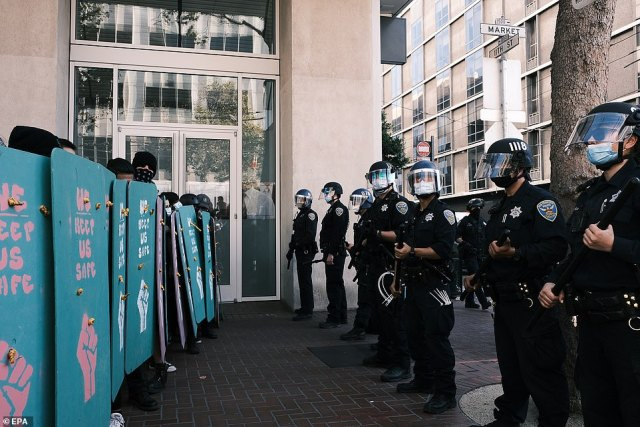 Counterprotesters hold shields up in a wall facing a wall of cops
