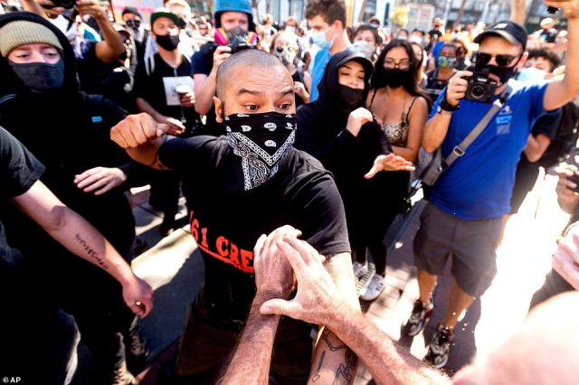 A counterprotester is seen about to hit a participant of the pro-Trump rally