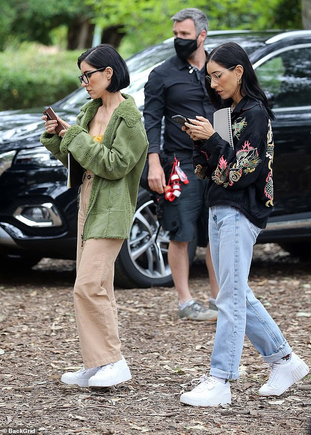 Walk this way! The superstars appears to be distracted by something on their phone as they strolled along in matching footwear