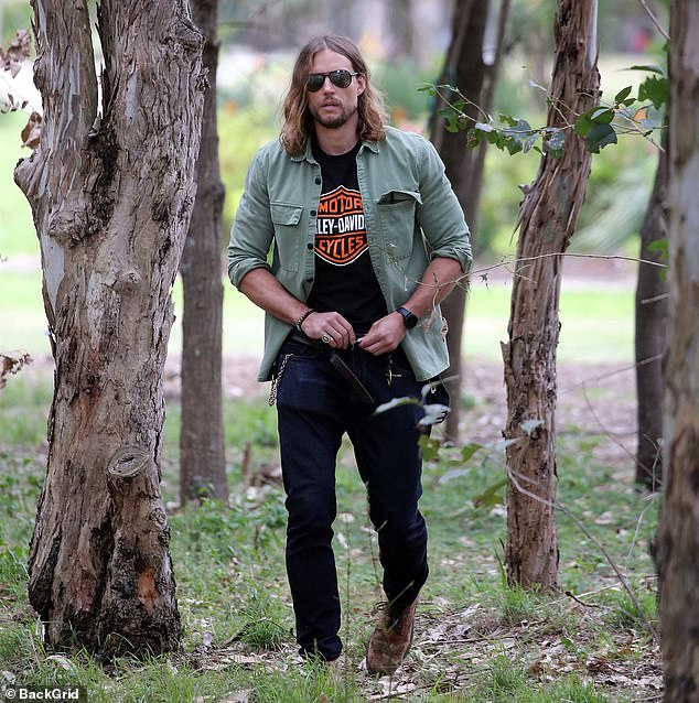 Reality bites:The blonde hunk was no doubt relieved as he went about his business.David wore dark blue jeans, a classic Harley-Davidson T-shirt and a green button-up shirt open, rolled up at the sleeves, denoting he had work to do