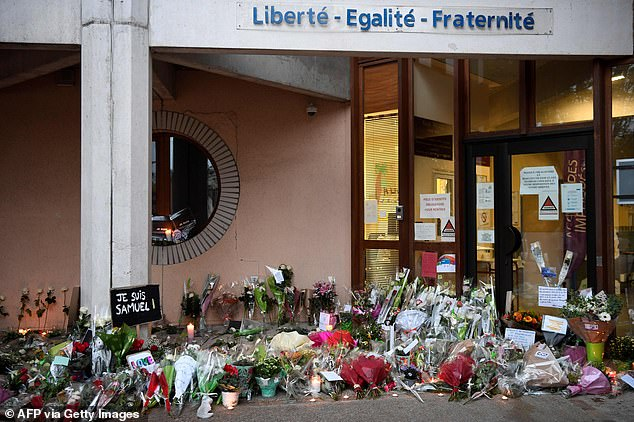 Signs read 'Je suis Samuel' outside the school in Conflans-Sainte-Honorine in tribute to Mr Paty, who was killed on Friday