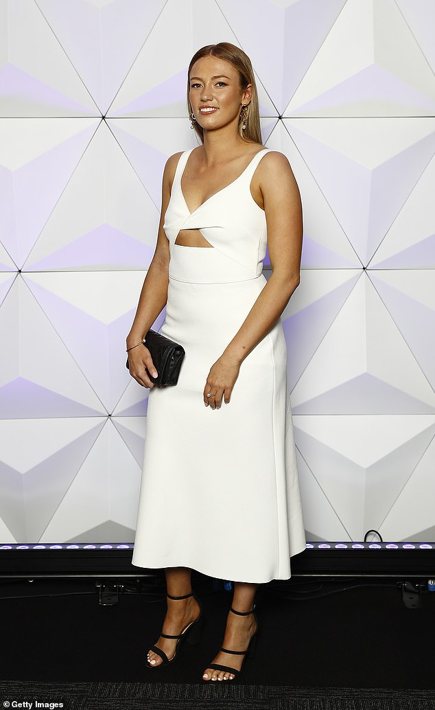 Peek:Georgia chose a fitted white dress with cut-outs that showed off a hint of skin, white carrying a smart black clutch with matching strappy black heels