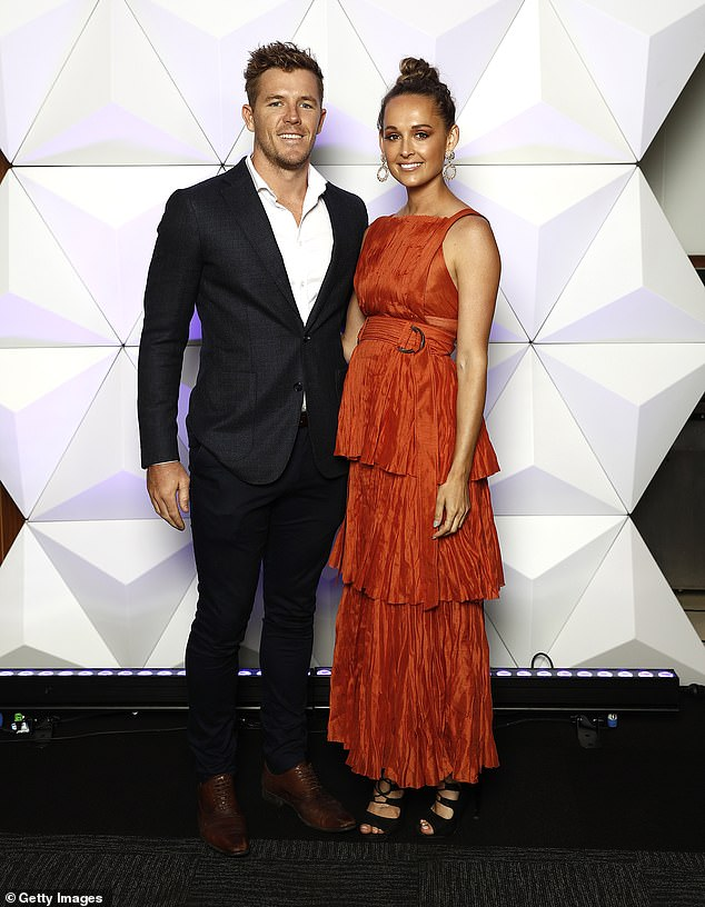 Bright:Luke Parker of the Swans and partner Kate Lawrence were eye-catching on the night.Luke looked dapper in a black suit open to a white shirt sans tie and a brown dress shoes
